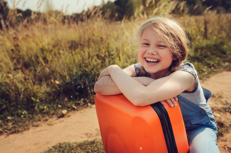 Muchacha feliz del niño con la maleta anaranjada que viaja solamente el vacaciones de verano Niño que va al campamento de verano imagenes de archivo