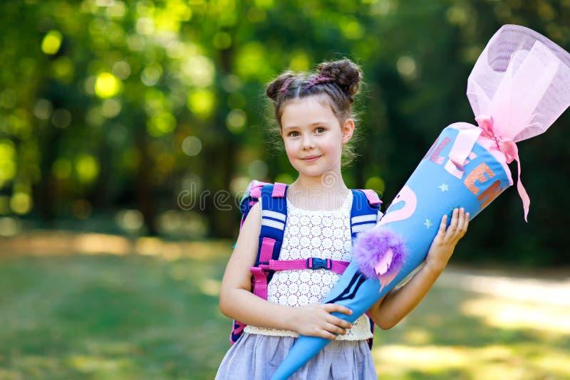 Muchacha feliz del niño con la mochila o taleguilla y bolso de escuela grande o cono tradicional en Alemania para el primer día d fotografía de archivo