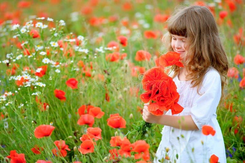 Muchacha feliz del niño con un ramo de amapolas rojas que gozan al aire libre imagen de archivo