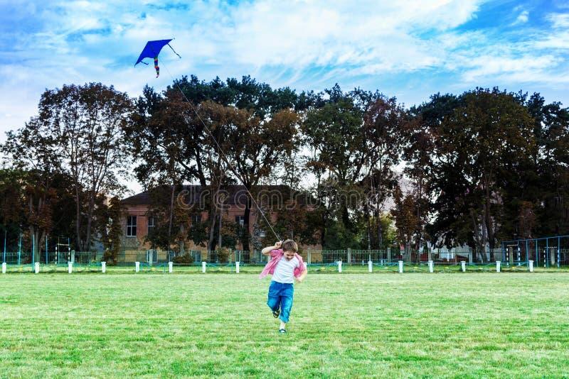Muchacha feliz del niño con una cometa que corre en prado en verano en naturaleza imagenes de archivo