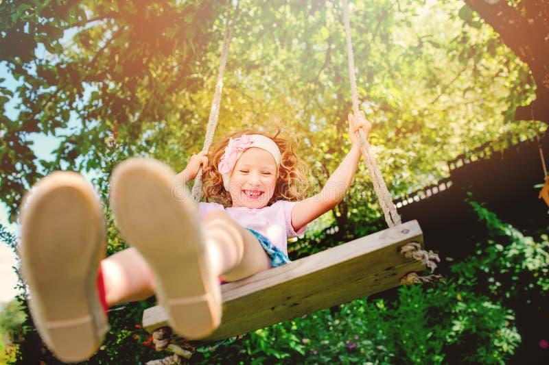 Muchacha feliz del niño en el oscilación en jardín soleado del verano fotos de archivo libres de regalías