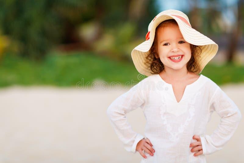 Muchacha feliz del niño en el vestido blanco en la playa en el mar del verano imagen de archivo
