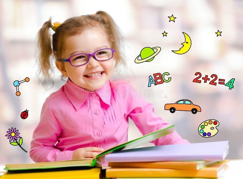 Muchacha feliz del niño en libros de lectura de los vidrios en biblioteca fotos de archivo