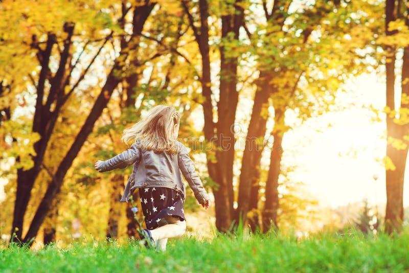 Muchacha feliz del niño que corre en parque del otoño Niña que se divierte en otoño Niñez feliz Muchacha elegante que juega en el imagen de archivo