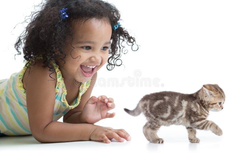 Muchacha feliz del niño que juega con el gatito fotos de archivo libres de regalías