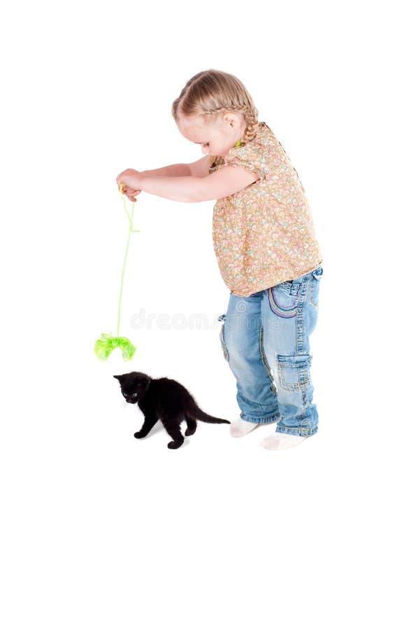 Muchacha feliz del niño que juega con el gatito del gato negro foto de archivo