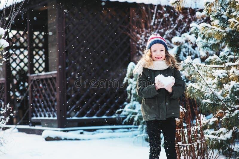 Muchacha feliz del niño que juega con nieve en paseo nevoso del invierno en patio trasero fotos de archivo