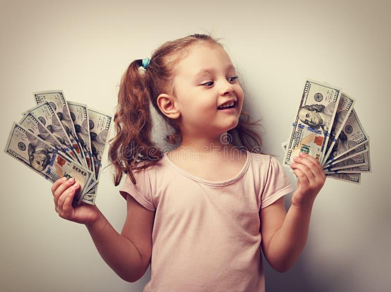 Muchacha feliz del niño que lleva a cabo dólares del efectivo y que mira con sonrisa Vint imagen de archivo libre de regalías