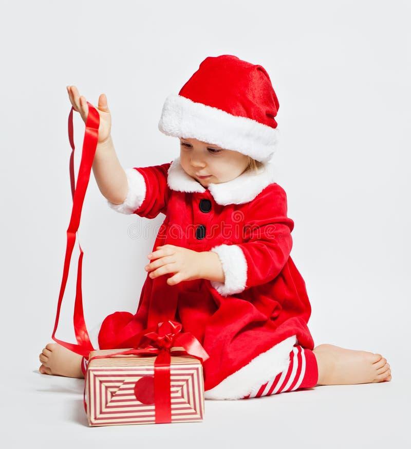 Muchacha feliz del niño que lleva el sombrero de Papá Noel con la caja de regalo de la Navidad foto de archivo libre de regalías