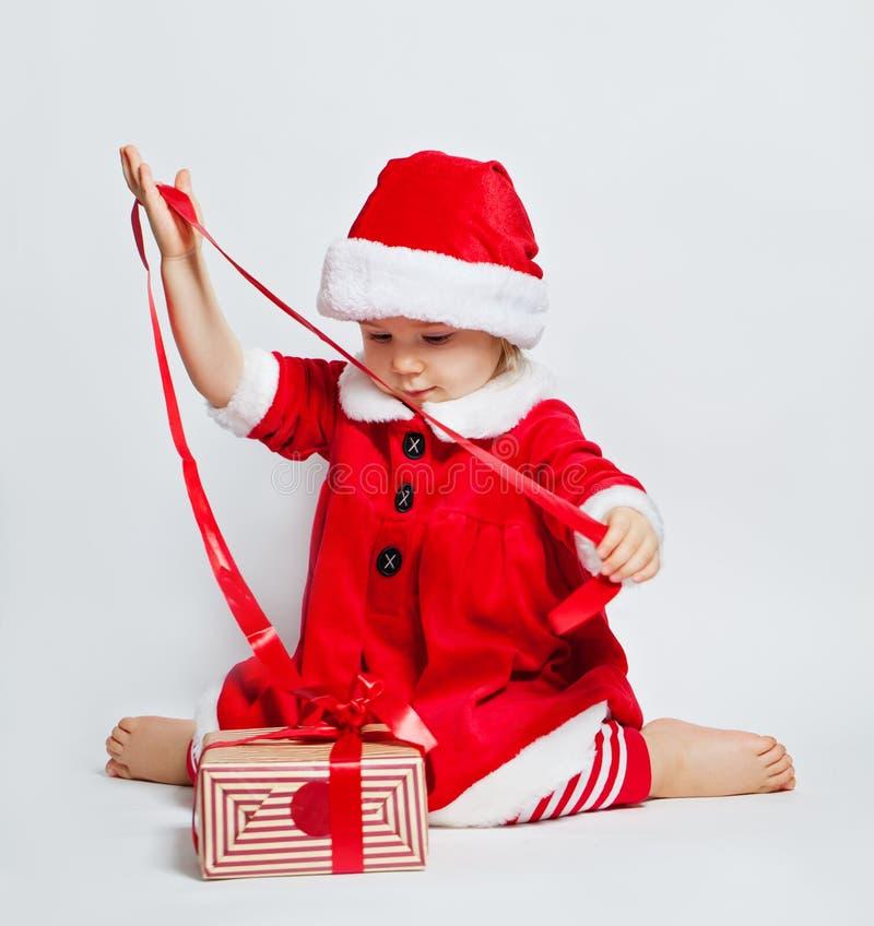 Muchacha feliz del niño que lleva la caja de regalo de apertura de la Navidad del sombrero de Papá Noel foto de archivo