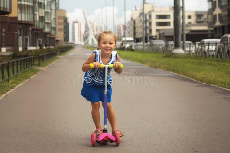 Muchacha feliz del niño que monta una vespa en el verano en el camino foto de archivo