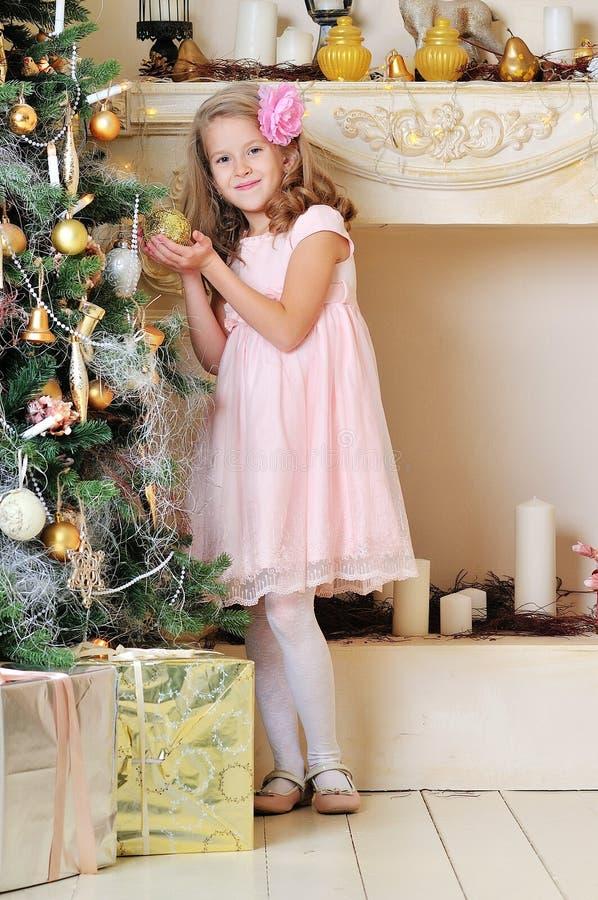 Muchacha feliz del niño que ríe en sitio sobre el árbol de navidad fotografía de archivo