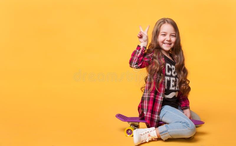 Muchacha feliz del niño que ríe mientras que se sienta en el monopatín fotos de archivo