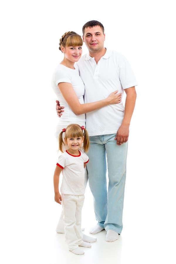 Muchacha feliz del niño que se coloca delante de padres foto de archivo