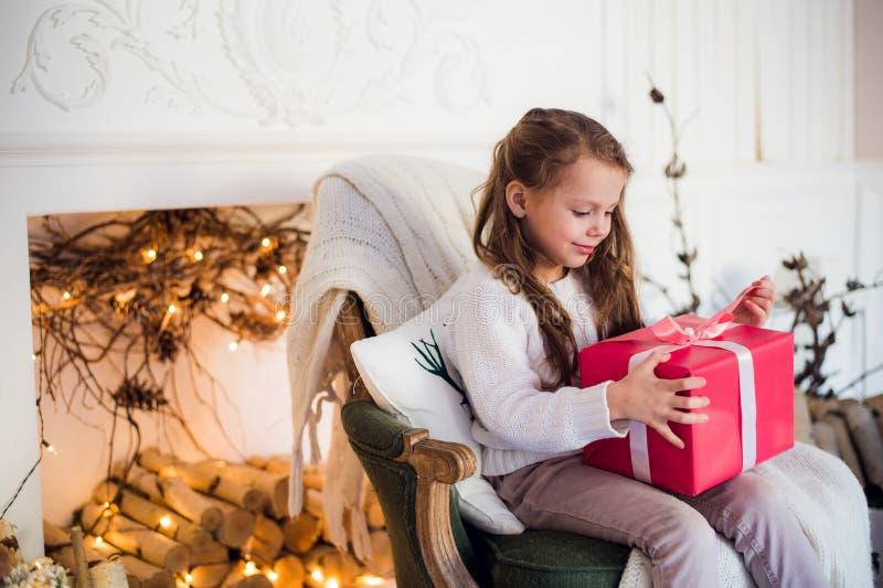 Muchacha feliz del niño que se sienta en la butaca cubierta con una manta contra la chimenea adornada de la Navidad foto de archivo
