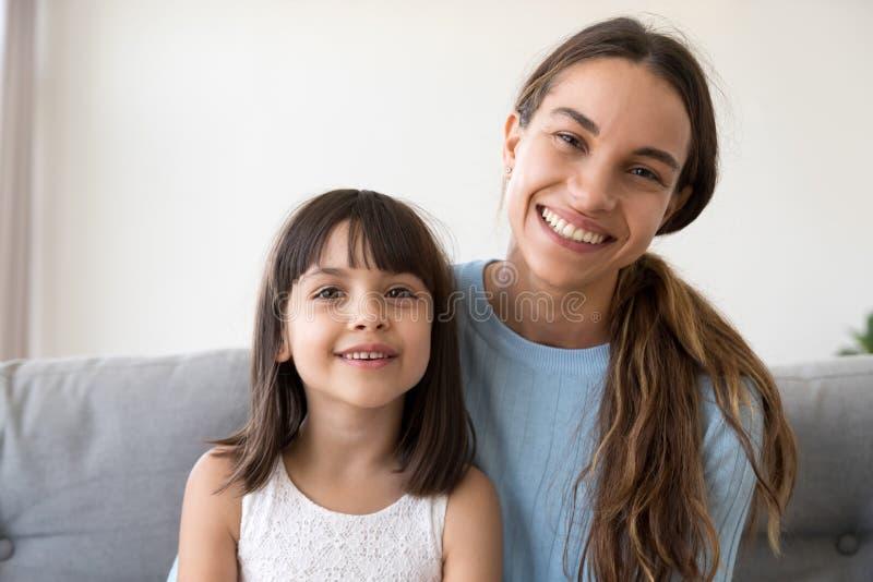 Muchacha feliz del niño y madre sonriente que miran la cámara, retrato fotografía de archivo