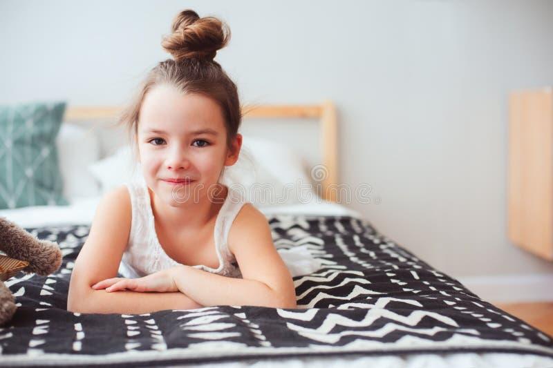 muchacha feliz del pequeño niño que miente en su cama por la mañana, despertando en sitio cómodo con la ropa de cama moderna fotografía de archivo