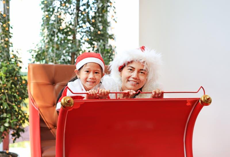 Muchacha feliz del pequeño niño y su madre en el vestido del traje de santa que se sienta en fondo rojo de la Navidad del trineo  fotos de archivo