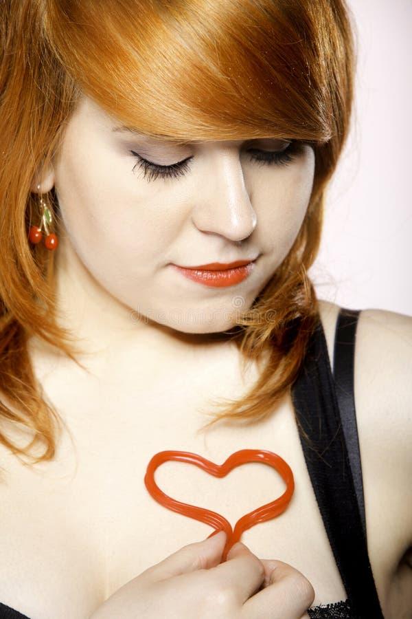 Muchacha feliz del redhair con símbolo del amor del corazón en pecho fotos de archivo
