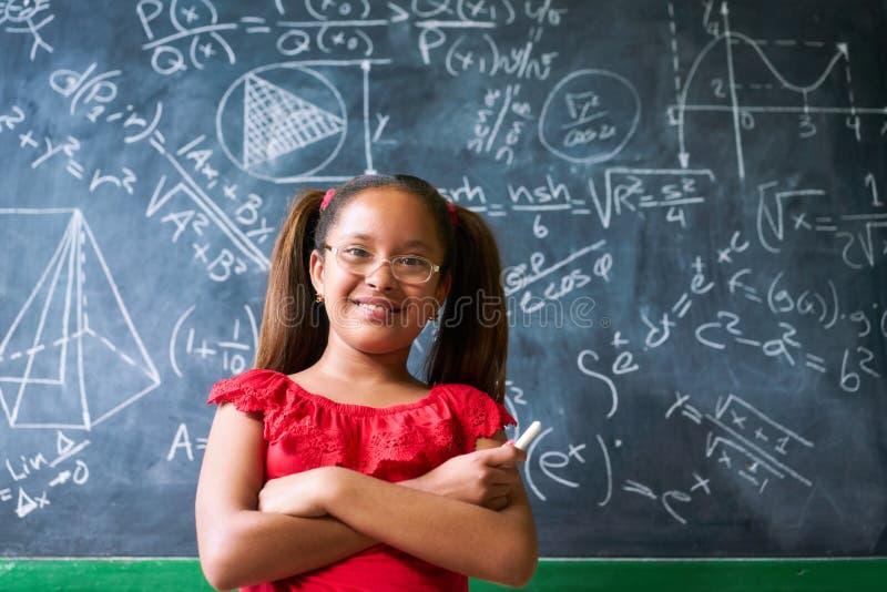 Muchacha feliz del retrato que resuelve problema de matemáticas complejo en la pizarra imagenes de archivo