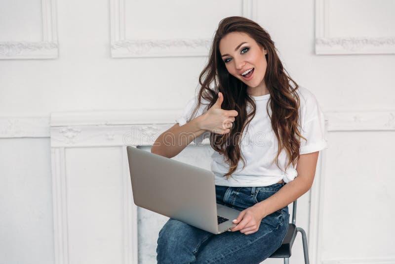 Muchacha feliz después de que una transacción acertada disfrute y mire el goog de la demostración de ordenador, muestra aceptable fotos de archivo
