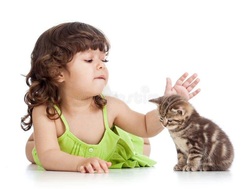 Muchacha feliz divertida del niño que juega con el gatito del gato imagen de archivo libre de regalías