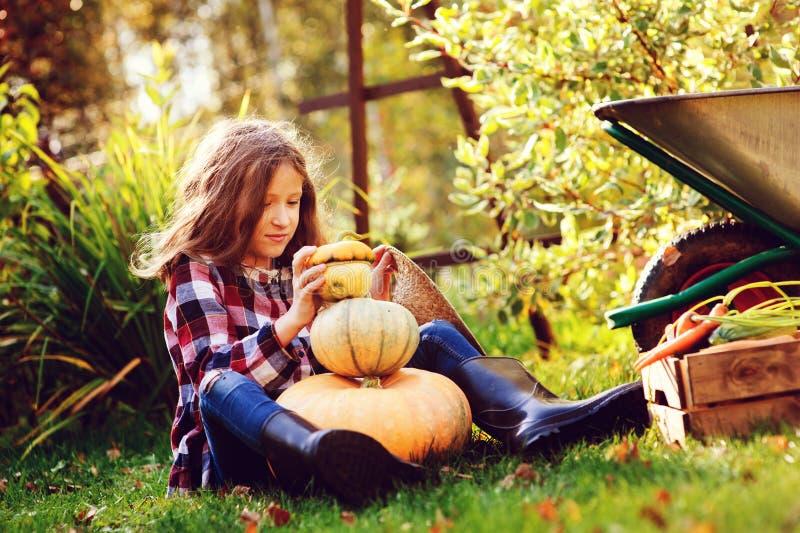 Muchacha feliz divertida del niño que juega con las calabazas y el ` constructivo del muñeco de nieve del ` en jardín del otoño foto de archivo libre de regalías