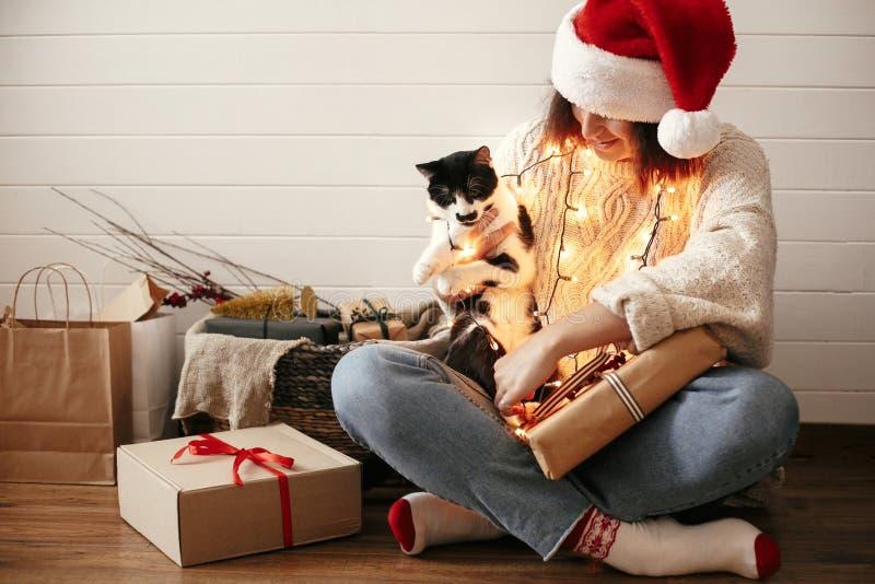 Muchacha feliz elegante en el sombrero de santa que sonríe y que juega con el gato lindo en luces de la Navidad festivas en el fo foto de archivo