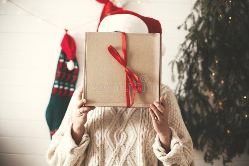 Muchacha feliz elegante en el sombrero de santa que sostiene la caja de regalo de la Navidad delante de la cara en fondo del árbo foto de archivo libre de regalías