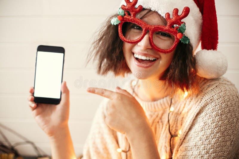 Muchacha feliz elegante en vidrios festivos con los cuernos del reno que sonríen y que muestran a teléfono la pantalla vacía en l fotografía de archivo