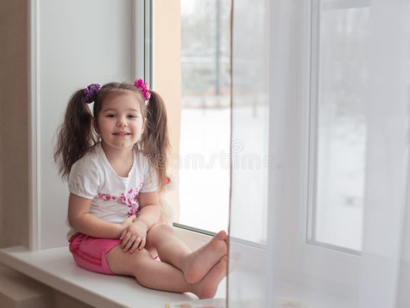 Muchacha feliz en alféizar imágenes de archivo libres de regalías