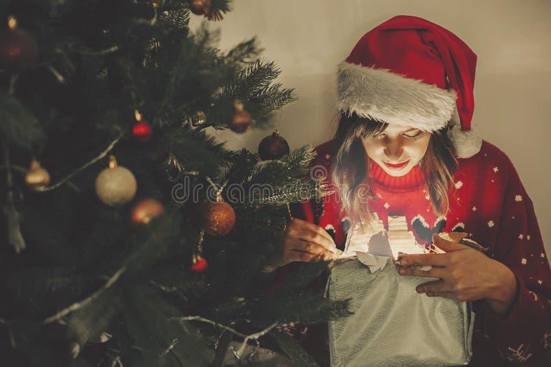 Muchacha feliz en caja de regalo mágica de la Navidad de la abertura del sombrero de santa en el oro fotos de archivo libres de regalías