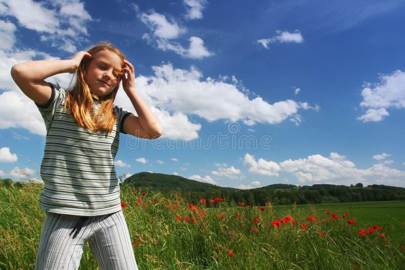 Muchacha feliz en campo de las amapolas foto de archivo libre de regalías