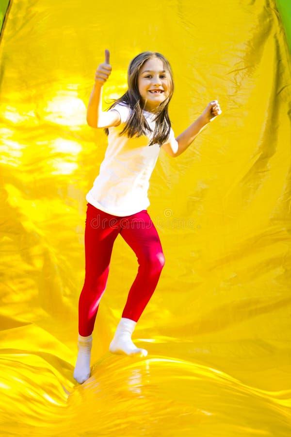 Muchacha feliz en castillo inflable fotos de archivo