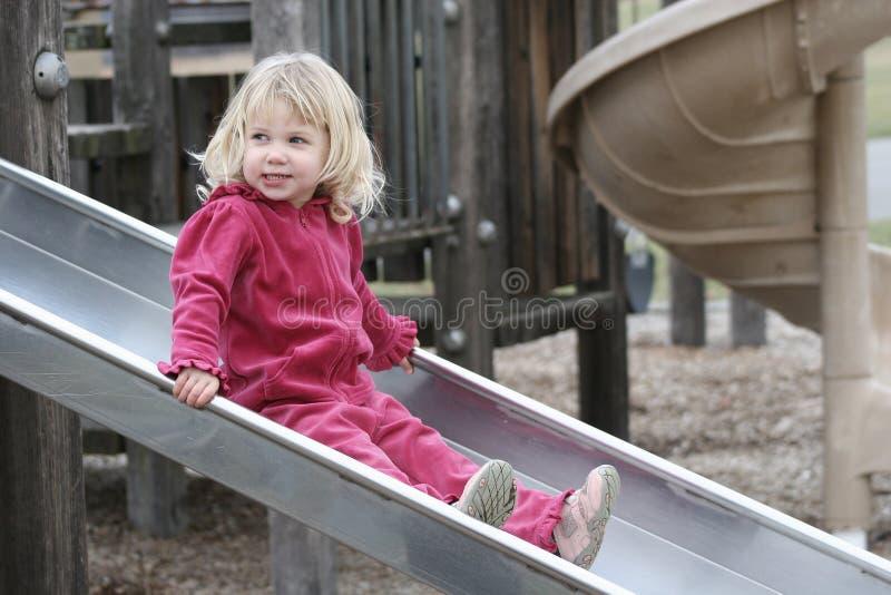 Muchacha feliz en diapositiva en el patio 2 fotografía de archivo