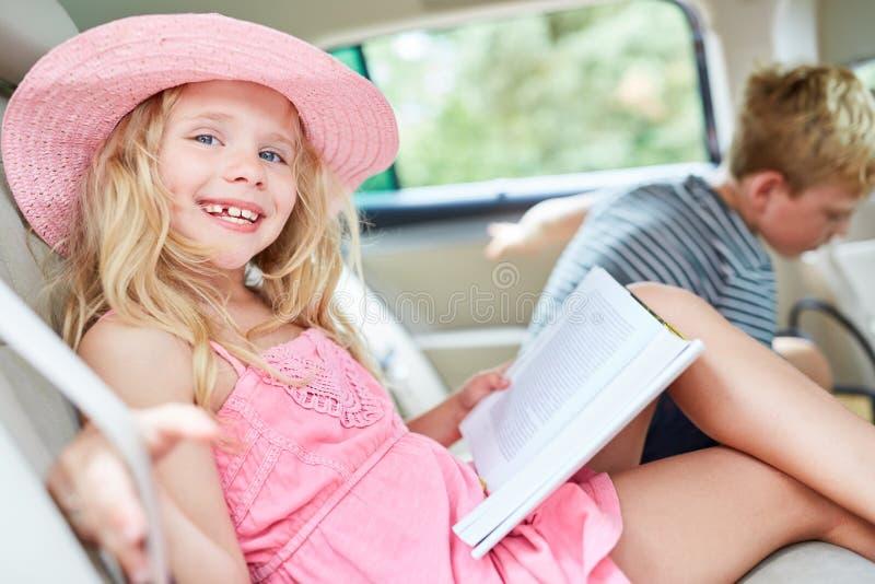 Muchacha feliz en el coche con un libro imagenes de archivo