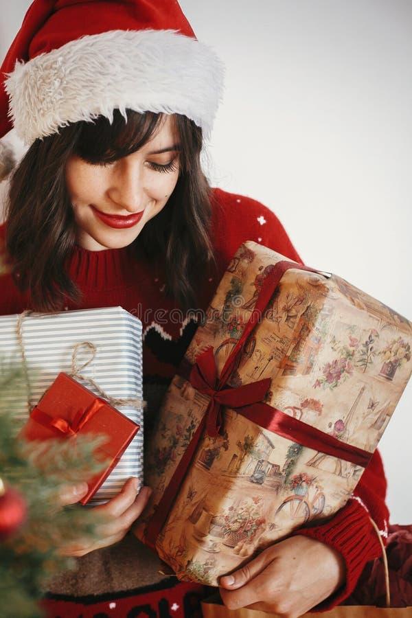 Muchacha feliz en el sombrero de santa que sostiene muchas cajas de regalo en el beauti de oro fotografía de archivo