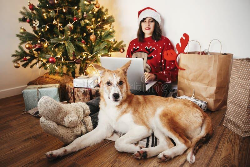 Muchacha feliz en el sombrero de santa que trabaja en el ordenador portátil y que se sienta con lindo fotos de archivo libres de regalías