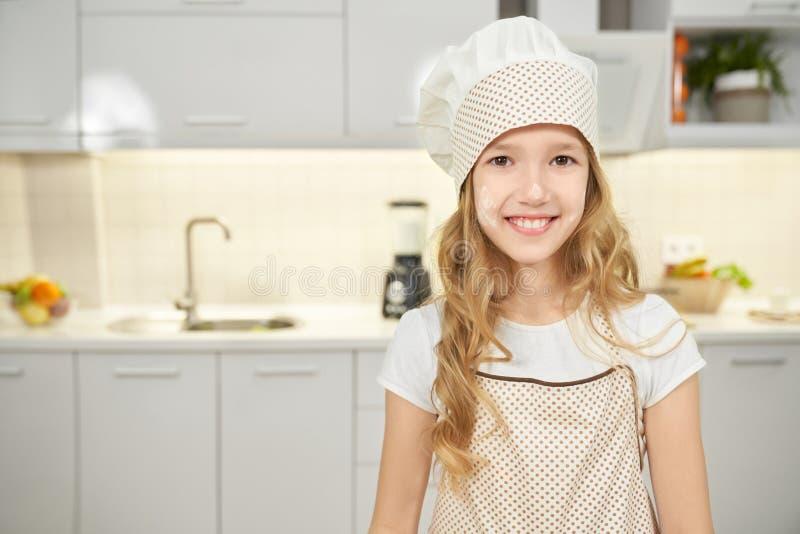 Muchacha feliz en el sombrero del delantal y del cocinero que presenta en cocina fotos de archivo