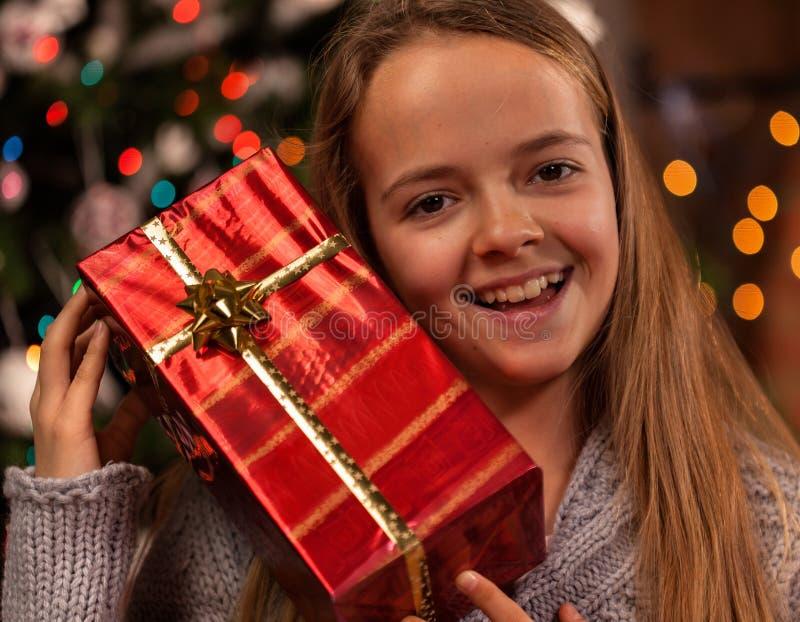 Muchacha feliz en el tiempo de la Navidad con un presente imagen de archivo