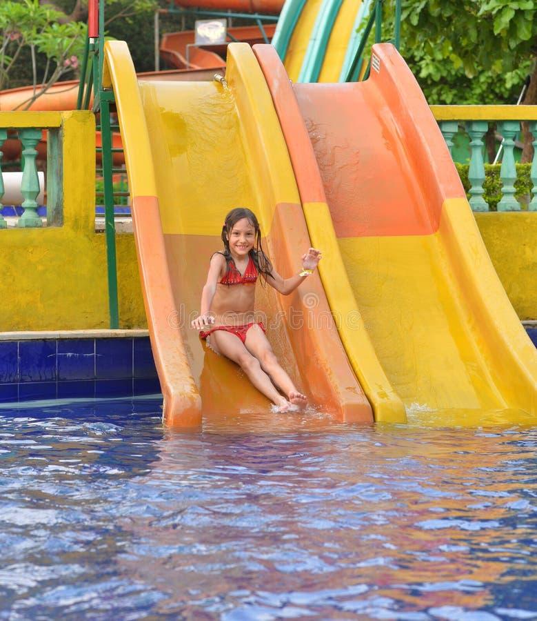 Muchacha feliz en el tobogán acuático foto de archivo