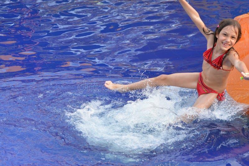 Muchacha feliz en el tobogán acuático imagen de archivo libre de regalías
