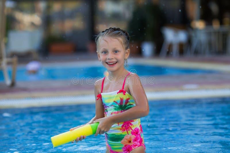 Muchacha feliz en el traje de baño que tira para arriba con el arma de agua foto de archivo