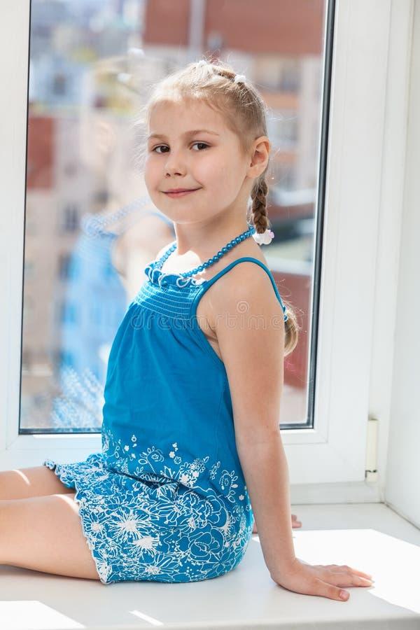 Muchacha feliz en el vestido azul que se sienta en alféizar en luz del sol imagenes de archivo
