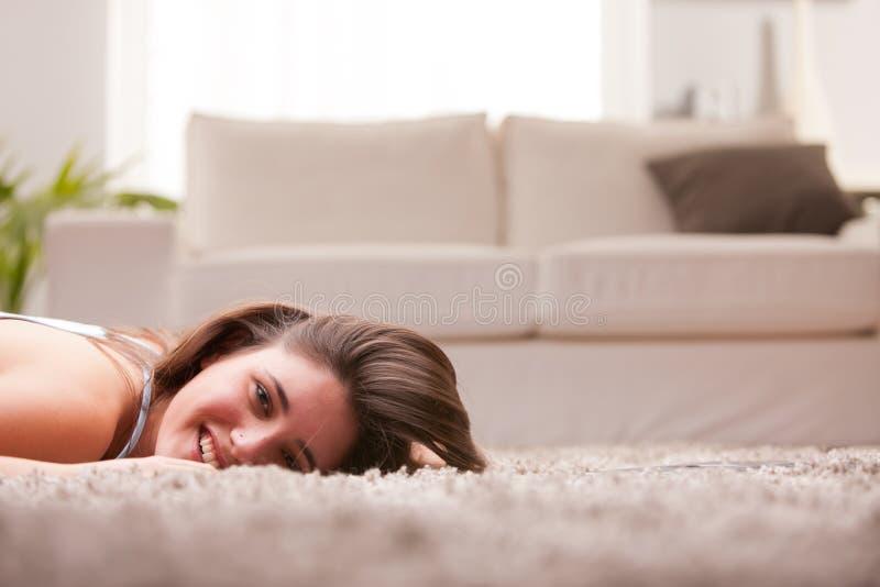 Muchacha feliz en la alfombra en su sala de estar fotos de archivo libres de regalías