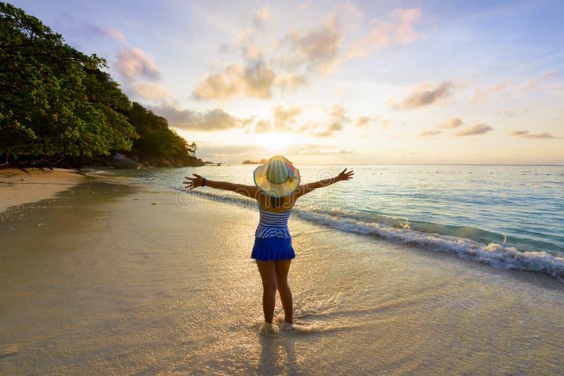 Muchacha feliz en la playa en la salida del sol fotos de archivo