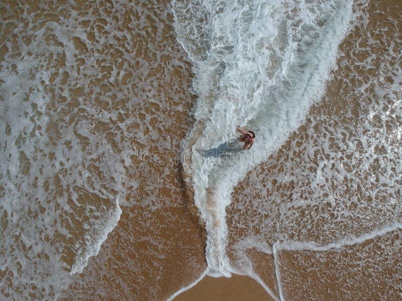 Muchacha feliz en la playa en forma de olas oceánicas arriba imagen de archivo