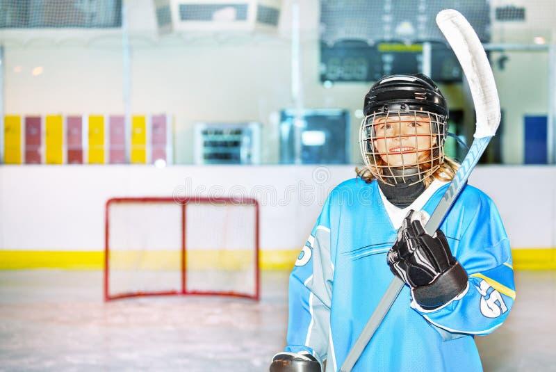 Muchacha feliz en la presentación uniforme del hockey con el palillo fotografía de archivo