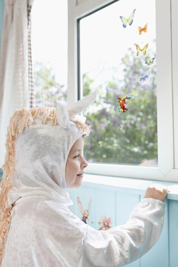 Muchacha feliz en las mariposas de Unicorn Costume Looks At Artificial fotografía de archivo