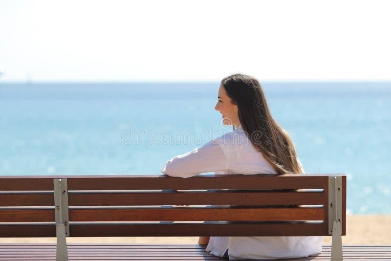 Muchacha feliz en un banco que comtempla el océano en la playa imagen de archivo